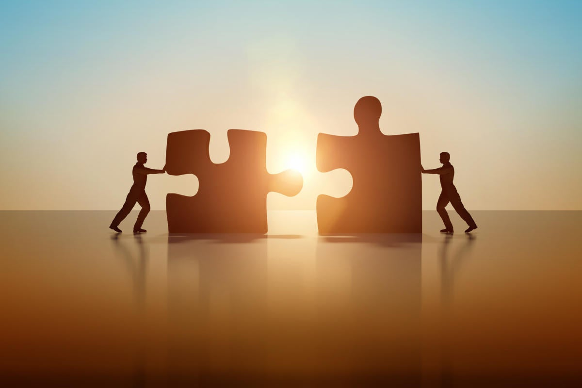 CSO > Two business people connecting and solving a puzzle.