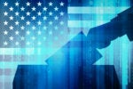 Election security  >  Backlit hand drops a vote in a ballot box with US flag + binary code overlay