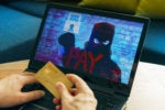 Ransomware  >  A masked criminal ransoms data for payment.