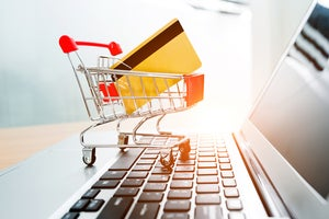 A miniature shopping cart with a credit card sits on computer keyboard.