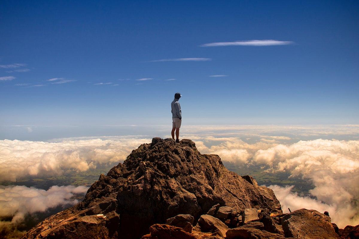 Staring from a peak over cloud-covered landscape below  >  Mount Taranaki, New Zealand