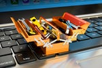 Miniature tools + toolbox toolkit on a laptop keyboard.