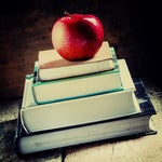 A stack of school books sits on a desk, with an apple on top. [Education/Learning]