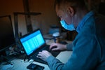 A laptop user wears a mask as protection from viruses, pollutants, toxins / COVID-19 pandemic