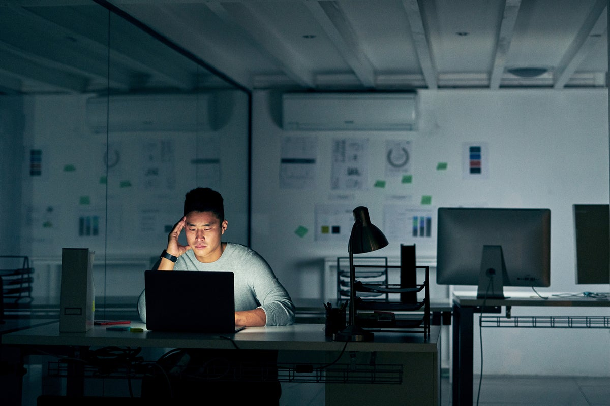 A stressed employee works alone in a dimly lit office.