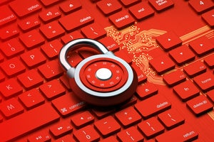 A red padlock sits on a red keyboard and golden circuit background.