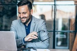 businessman looking happy in front of laptop