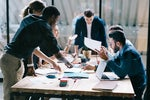 A group discussion takes place around a table in an office workspace.